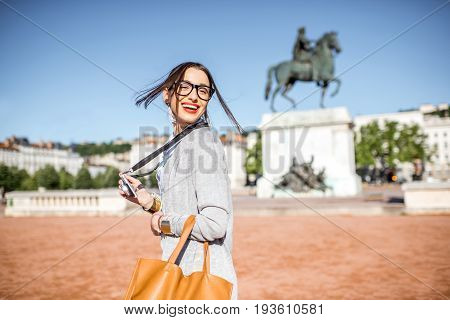 Young woman with photocamera walking on the famous Bellecour square with Louis king statue traveling in Lyon city in France