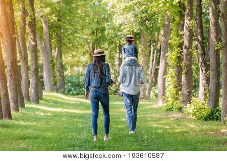 Back View Of Young Family Walking In Forest, Father Carrying His Daughter On Shoulders