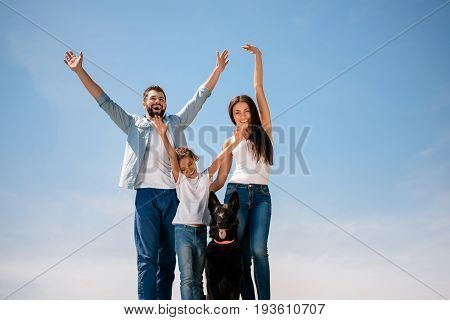 Happy Young Family Standing Together With Dog And Smiling At Camera Outdoors