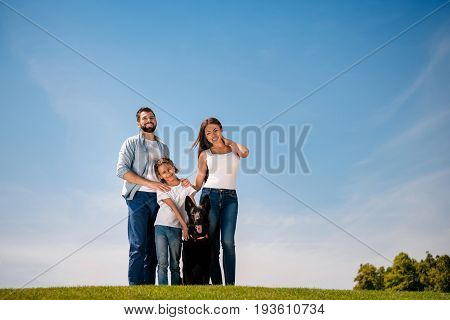 Happy Young Family With One Child Having Fun With Dog On Green Lawn