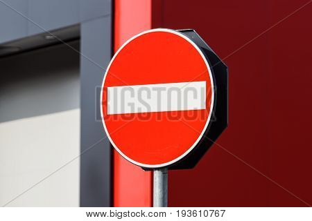 Round red road sign on metal pole. No Entry road-sign mounted on urban roadside .