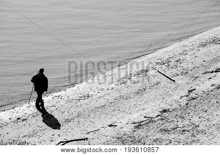 Old man walking. Silhouette of old man with stick walking on riverside. Black and white. Loneliness. Sadness. Depression.