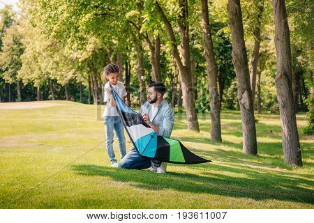 Father Helping Daughter With Kite While Spending Time Together In Park