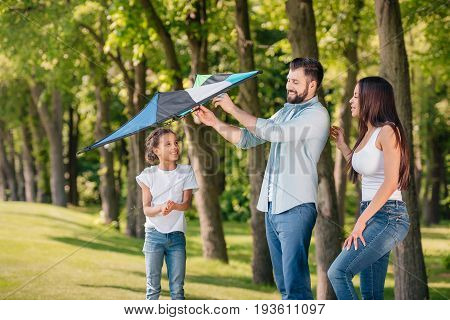 Father Helping Daughter To Launch A Kite While Spending Time Together In Park