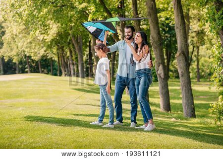 Family Launching Kite While Spending Time Together In Park