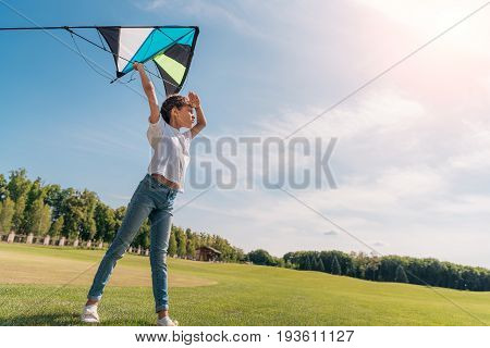 side view of little girl wanting to launch a kite on green lawn