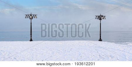 Snowy Embankment Along The Misty River With Lanterns At The Foggy Morning - Winter Landscape.