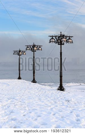 Snowy Embankment Along The Misty River With Lanterns At The Foggy Morning - Winter Landscape. Iii