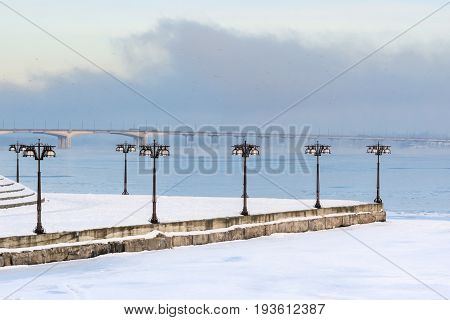 Snowy Embankment Along The Misty River With Lanterns At The Foggy Morning - Winter Landscape. V