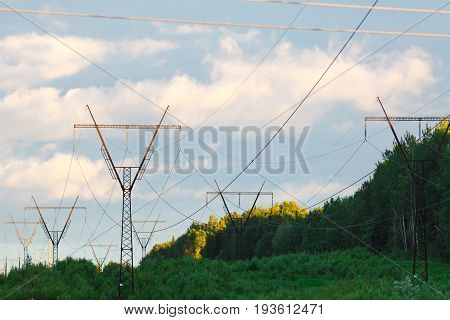 High Voltage Power Pylons Against Blue Sky And Sun Rays