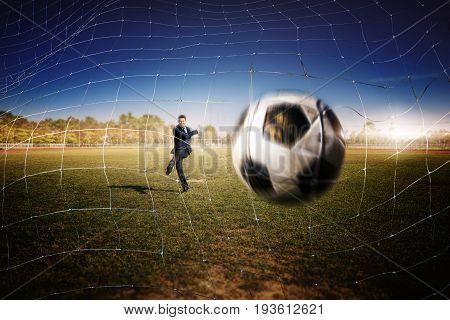 Asian Businessman Play Football In The Stadium Foolball.