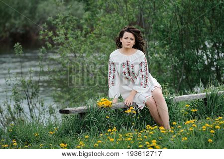 Portrait of a beautiful girl in Slavic clothes. Young woman with a bouquet of dandelions sitting on a wooden bench on the river bank. Summertime