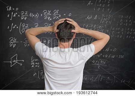 Young Man Is Solving Mathematical Problem On Blackboard And Is C