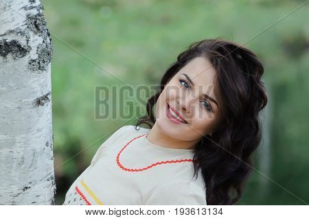 Portrait of a beautiful smiling girl in Slavic clothes. Summertime