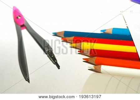 Photo of crayons with compass on exercise book and a paper