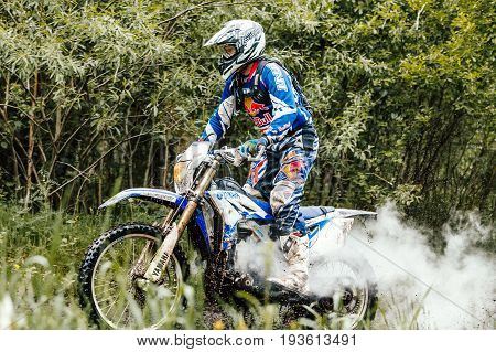 Kyshtym Russia - June 18 2017: motorcycle rider in forest of exhaust gas back during Ural Cup in Enduro