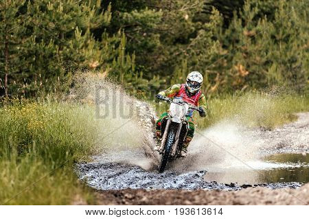 Kyshtym Russia - June 18 2017: enduro athlete on motorcycle crosses a water puddle during Ural Cup in Enduro