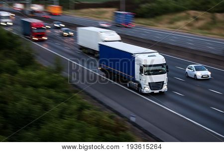 Lorries in motion. Evening traffic on the motorway.