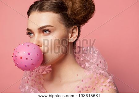 Charming girl dressed in fancy dress blowing pink balloon decorated with sparkles.