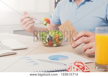 Healthy business lunch in modern office. Unrecognizable man cropped image, businessman in t-shirt at working place eating salad