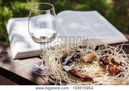 Glass with white wine stands near open book, orkscrew with cork and pieces of chocolate lie on sawdust, romantic background