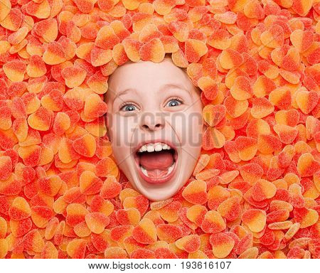 From above view of little kid lying in fruit jelly and shouting loud at camera.
