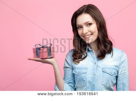 Young brunette in denim shirt holding small giftbox on palm and looking at camera