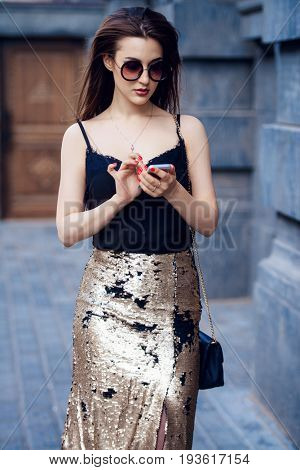 Beautiful brunette woman talking on her cell phone walking down the city street. Beauty, fashion outdoor.