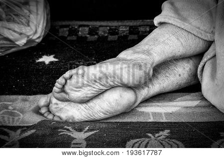 Bare feet of homeless person sleeping on the street. Black and white. Homelessness. Social. Documentary. Street.