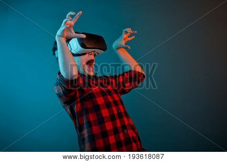 Little boy in checkered shirt wearing VR glasses and looking scared on blue background.