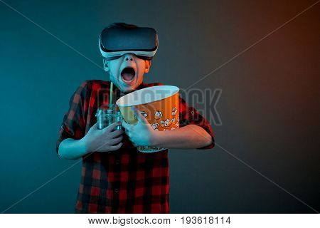 Boy wearing VR glasses looking scared while holding popcorn and cola in hands.