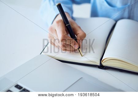 A woman at her desk writing in a notebook.
