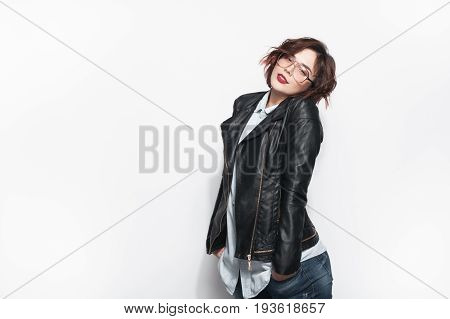 Beautiful young brunette in black leather jacket anf glasses posing with hands in pockets on white background.