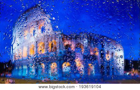 Colosseum of Rome - Might and Glory of Ancient Rome. A view of the city from a window from a high point during a rain. Rain drops on glass. Focus on drops