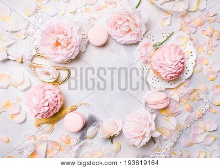 Pink cupcakes with roses and holiday decor in frame. Festive and bright. Wedding Celebration concept. Copy space