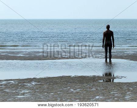 statue facing the sea at crosby beach merseyside