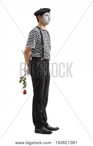 Full length profile shot of a sad mime with a rose waiting in line isolated on white background