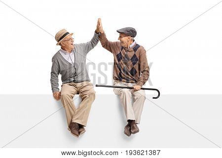 Seniors sitting on a panel and high-fiving each other isolated on white background