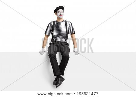 Mime artist sitting on a panel isolated on white background