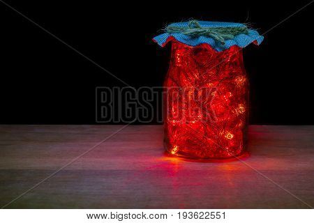 Red LED light in the glass bottle in darkness on brown wood table. Keep electrical energy for economical use. Concept of love the world and energy saving.
