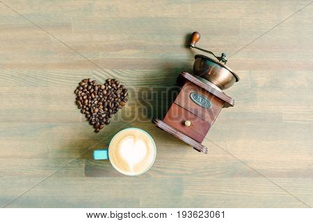 A cup of cappuccino, coffee grinder and heart of beans on wooden table.