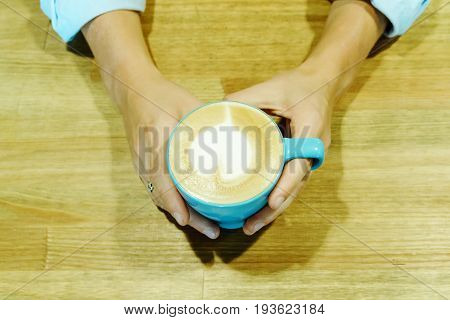 Heart Froth Milk Cappuccino Cup. Girl Hands Holding An Aroma Drinking On Wooden Table