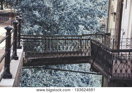 metal bridge connecting sidewalk and commercial tenements blue tree