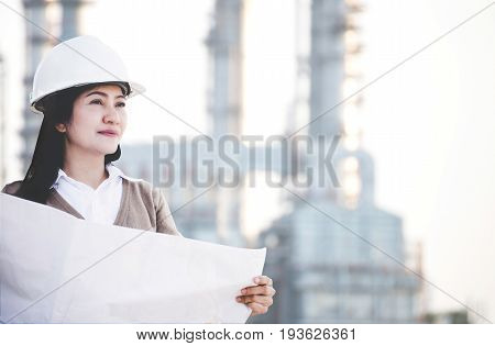 Engineer asia woman with hard hat holding blue print paper looking away inspecting progress at construction power plant site safety control. Engineer Concept.
