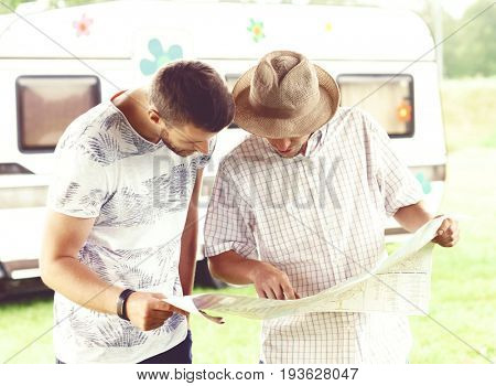 Good friends checking the map and planning their route. Trip, traveling, holiday, vacation concept.