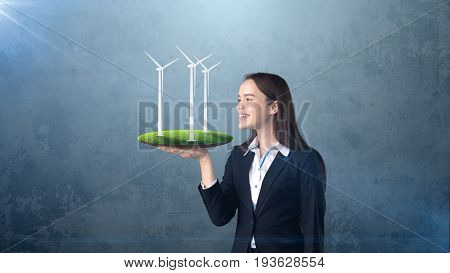Portrait Of Young Woman Holding Windmill On The Open Hand Palm, Over Isolated Studio Background. Bus