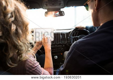 Rear view of woman showing tablet computer to man while sitting in car during test drive