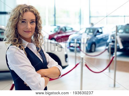 Portrait of smiling saleswoman with arms crossed standing in car showroom