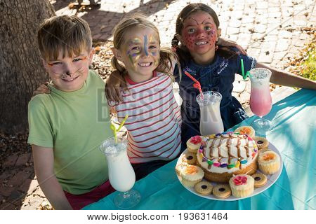 Portrait of happy friends with face paint sitting by food and drink at table