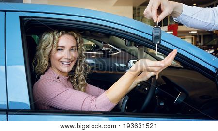Cropped image of hand giving keys to customer sitting in car at showroom